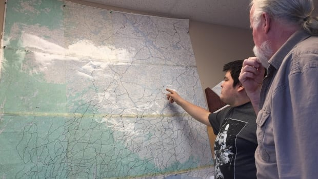 Randy Freeman, right, traditional knowledge specialist for the Yellowknives Dene First Nation, looks at a map showing hundreds of trails traditionally used by the First Nations' members.