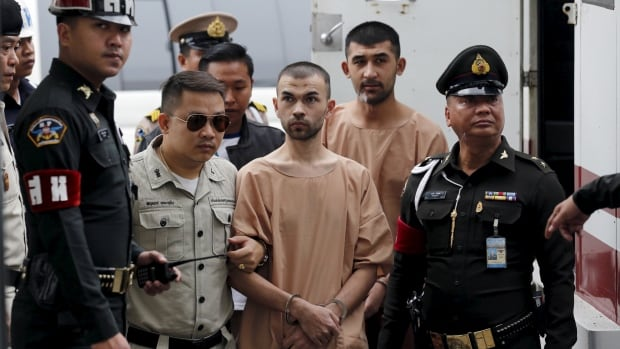 Suspects of last year's Bangkok blast Bilal Mohammed, centre, who is also known as Adem Karadag, and Yusufu Mieraili behind him are escorted by prison officers as they arrive at the military court in Bangkok on Tuesday.