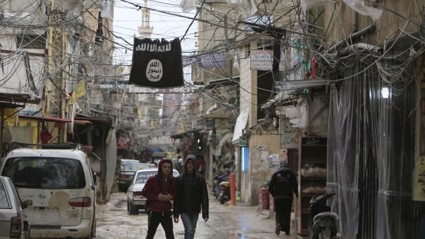 Youth walk under an ISIS flag in Ain al-Hilweh Palestinian refugee camp, near the port-city of Sidon, southern Lebanon, on Jan. 19, 2016.