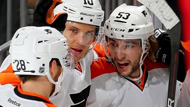 Flyers defenceman Shayne Gostisbehere, right, celebrates his first-period goal against the Devils on Tuesday night in Newark, N.J. Gostisbehere extended his points streak to 13 games, the second-longest by an NHL player this season and longest by a rookie since Colorado's Nathan MacKinnon (13 games) in 2013-14.