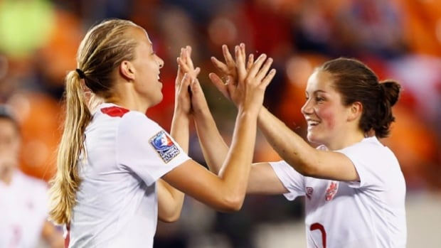 Rebecca Quinn, left, and Jessie Fleming of Canada celebrate during Tuesday night's 10-0 drubbing of Guatemala at the Olympic qualifying soccer tournament in Houston. Quinn and Nichelle Prince paced the attack with three goals apiece as the Canadians move on to Friday's semifinal against Costa Rica at 5:30 p.m. ET.