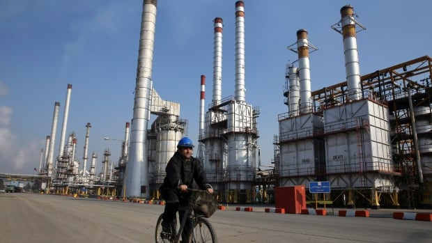 An Iranian oil worker rides his bicycle at the Tehran oil refinery in this December 2014 photo.