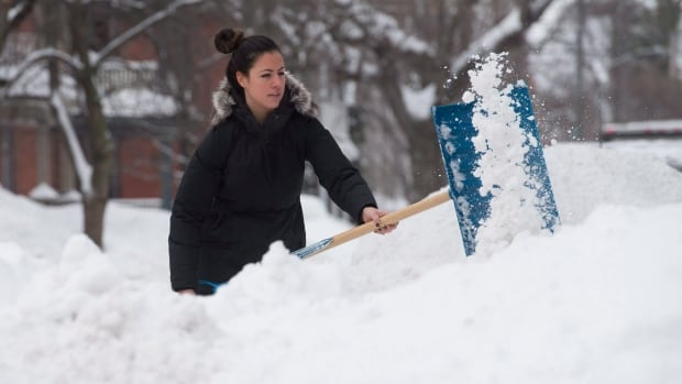 Alexandra Aversa clears snow from her driveway on Wednesday as she digs out after a winter storm dumped a record 51.2 centimetres of snow on the Ottawa area.