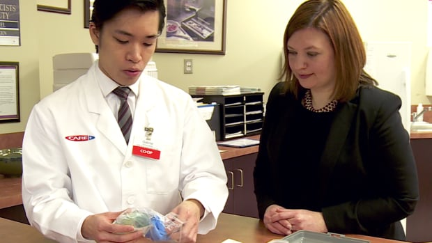Brandy Payne, associate minister of health, and a Calgary Co-op pharmacist, look at the contents of a naloxone kit, which contains two units of naloxone, two syringes, two alcohol swabs, two latex gloves, a one-way breathing mask and instructions.