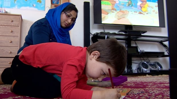 Victoria Ayanee watches her 4 year-old son, Bashir, draw at their home in Calgary.