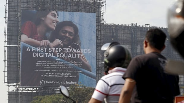 Motorists ride past a billboard displaying Facebook's Free Basics initiative in Mumbai. The app, which India banned, provides free but limited access to the internet.