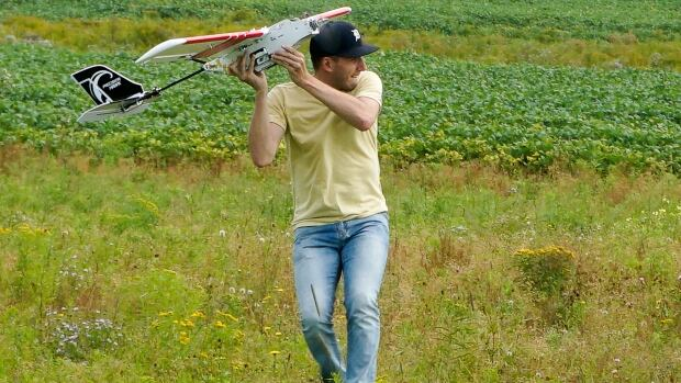 UPEI graduate student Derek Ellis launches an aerial drone to help collect geographical data.