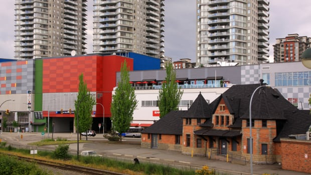The old CP Rail train station in New Westminster surrounded by a shopping mall and high rises.