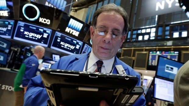 Trader Sal Suarino works on the floor of the New York Stock Exchange. Markets in New York and Toronto were lower Friday as oil prices reversed recent gains.