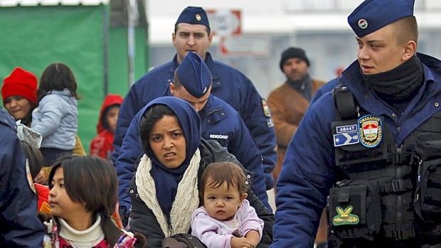 Hungarian border police marshall migrants at the transit camp on the Macedonia-Greece border near Gevgelija last month. Hungary wants to build a wall along the Serbian border to keep Syrian and other asylum seekers at bay.
