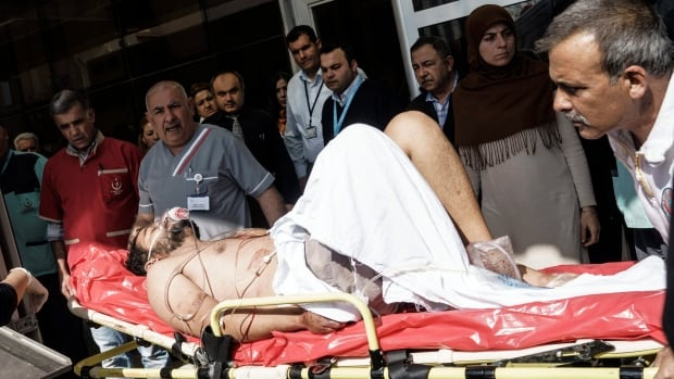Turkish medics carry a wounded Syrian to a hospital in Kilis, Turkey, Monday, Feb. 15, 2016. An airstrike destroyed a makeshift clinic supported by an international aid group in Azaz in northern Syria on Monday, killing and wounding several people, activists and aid group said.