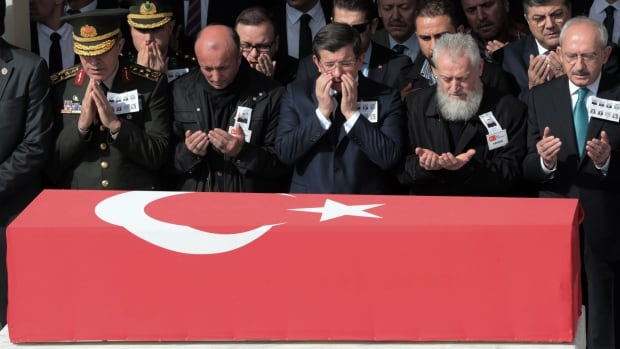 Turkish Prime Minister Ahmet Davutoglu, centre, main opposition leader Kemal Kilicdaroglu, right, Chief of Staff Gen. Hulusi Akar, left, and a family member of a victim attend funeral prayers for eight of the 28 victims in Ankara on Friday.