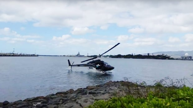 In this image taken from video shot by tourist Shawn Winrich, a helicopter can be seen crashing near Pearl Harbor, Hawaii, on Thursday.