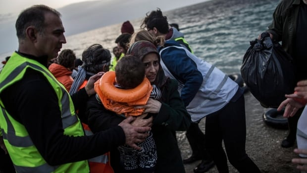 Volunteers assist refugees and migrants fleeing the conflict in Syria; speakers at the TED Conference argued that a new approach is needed to solve the crisis.