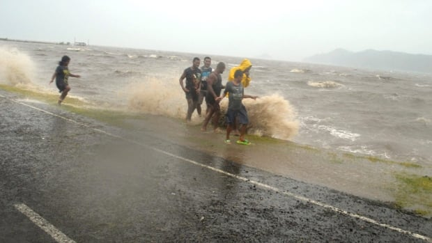 People are splashed by a wave whipped up by the encroaching cyclone in Labasa, Fiji, on Saturday.