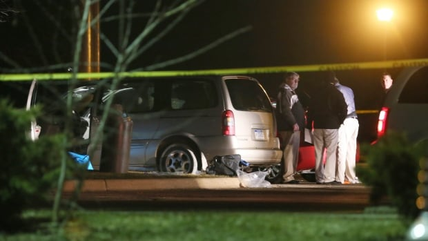 Police investigate the scene of one of the shootings, outside a Cracker Barrel restaurant in Kalamazoo, Mich.