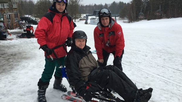 Alain Legault, sitting in a sit-ski at Owl's Head, says having skiing back in his life is 'a gift.' He's flanked by his son Hadrien and longtime volunteer Fred Cuplinskas.