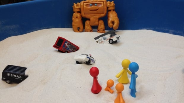 Children place their figures in a sand box, and play with them there under Toni King's supervision. They'll often act out scenes from their lives, King says.