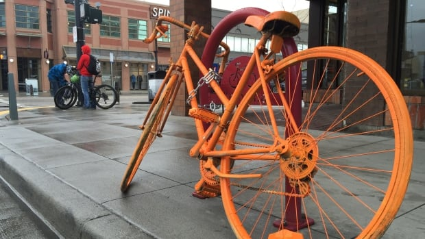 An orange bicycle chained chained to a bike rack in downtown Kelowna as part of guerilla marketing campaign for a new fitness studio