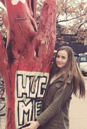 Madeline hugging a tree