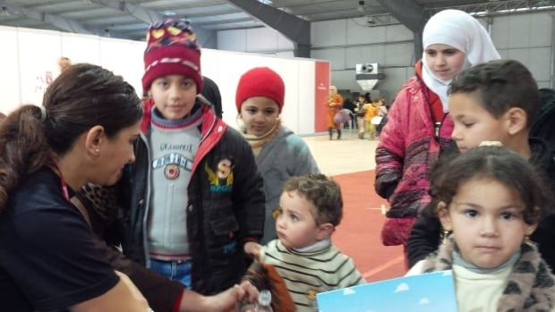 RCMP acting Sgt. Lina Dabit hands out water and colouring books to Syrian refugees in Jordan bound for Canada.