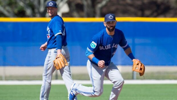 Jose Bautista, right, has landed in Dunedin, Fla., and at the Blue Jays' first official workout for pitchers and catchers on Monday, he told reporters that he has informed management what type of contract it would take for him to remain with Toronto but is still waiting for the Blue Jays' response. Bautista is entering the final year of his contract.