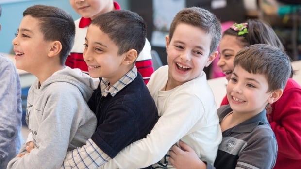 Syrian refugees Jamil Haddad, left, and Tony Batekh, 2nd left, George Louka and Edmon Artin, right, have some fun while they attend French classes at a school Wednesday, February 17, 2016 in Montreal.