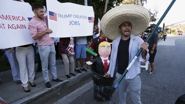 A Donald Trump protester carries a pinata of Trump past his supporters outside a campaign event in Los Angeles, in July 2015. Some Latinos say they are offended by Trump's insults about Mexican immigrants and are vowing to defend their community at the ballot box.