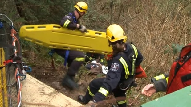Firefighters scramble down a steep embankment to rescue a women who fell.