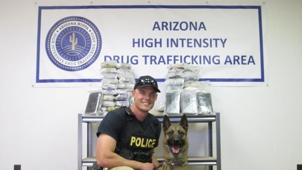 Police sniffer dog Amigo and his handler pose with the cocaine found during the bust.
