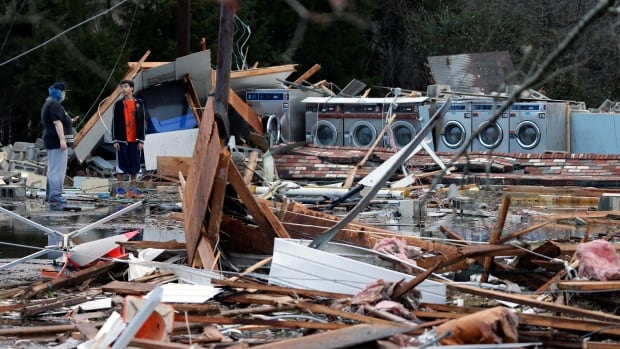 Spectators walk through debris left by a deadly storm that swept through Waverly, Va., Wednesday.