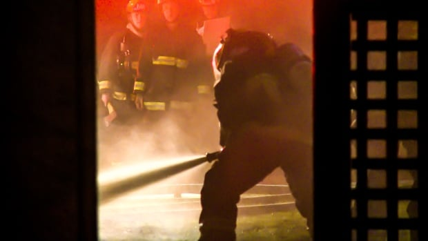 A firefighter battles a small fire in an East Vancouver house early Thursday morning.