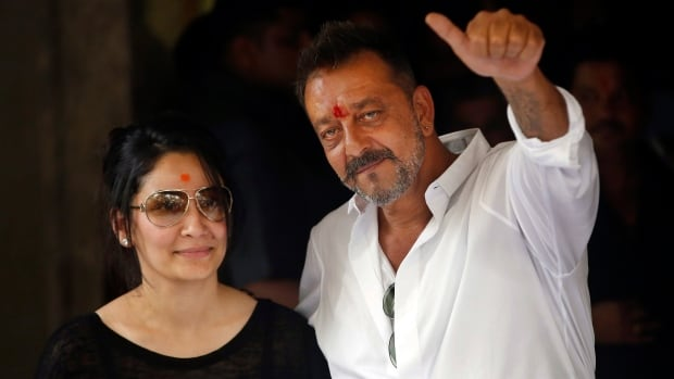 Sanjay Dutt, right, gestures to fans alongside his wife Maanyata as he arrived at his Mumbai residence on Thursday. The Bollywood actor left prison Thursday after completing a five-year sentence for illegal weapons possession in a case linked to the 1993 Mumbai terror attack.