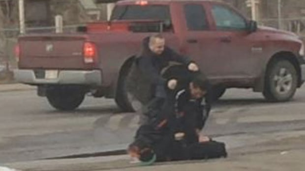 An image taken from a video shot by a bystander shows Edmonton police Const. Sasa Novakovic under attack as Eugene DeRose leaps to his defence.