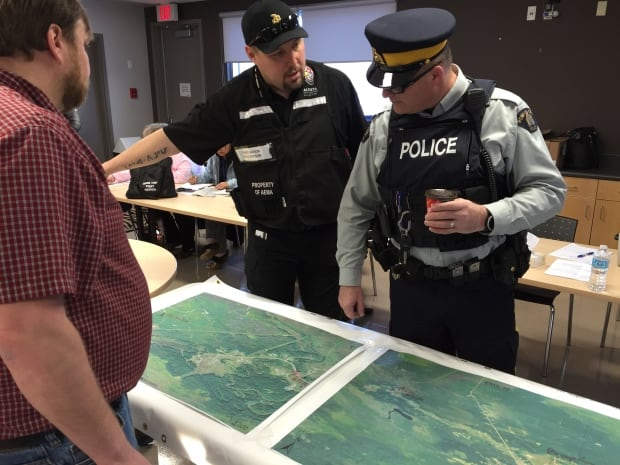 First Nation Field Officer Winston Delorme examines map with RCMP officer