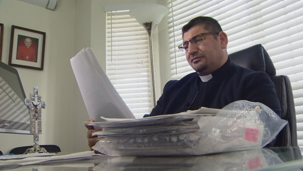 Father Sarmad Biloues, a Surrey priest and an Iraqi refugee himself, sifts through a stack of refugee sponsorship applications.