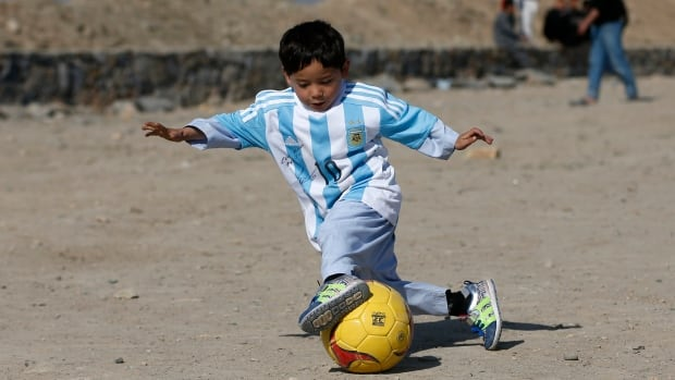 Five year-old Murtaza Ahmadi, an Afghan fan of Barcelona soccer star Lionel Messi, shows off his moves in a new signed shirt from his idol, in Kabul on Feb. 26.