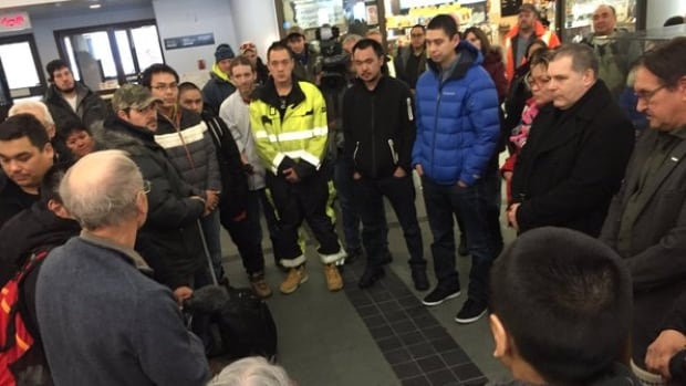 Iqaluit Rev. Mike Gardener, front left, leads a prayer circle for Nunavut crew members from the F/V Saputi. They arrived Friday afternoon in Iqaluit after their ship was damaged at sea.