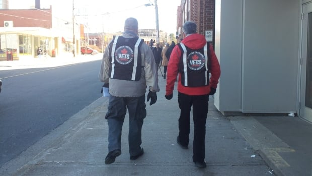 Two volunteers wear VETS Canada identification vests as they set out on the Boots on the Ground Walk in Halifax on Saturday.