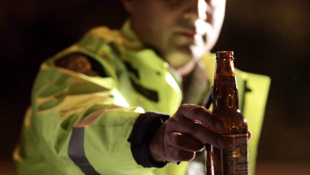 RCMP Const. Faz Majid removes an open bottle of beer from a motorist's car during a roadside check in Surrey, B.C.