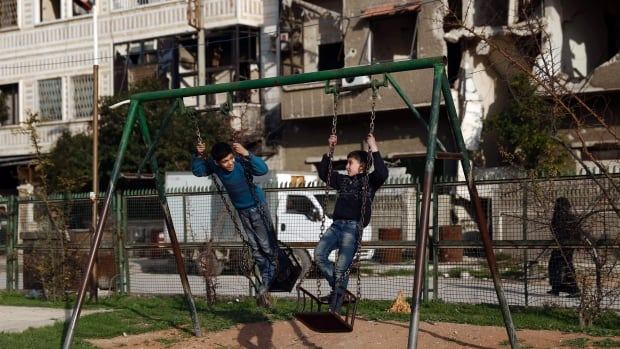 Syrian children play in the rebel-held town of Douma, on the eastern edges of the capital Damascus on Saturday, the first day of the truce.