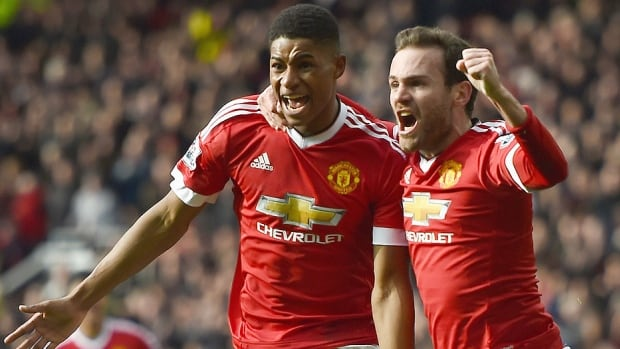 Manchester United's Marcus Rashford, left, celebrates his first of two goals against Arsenal with Juan Mata during Sunday's Premier League match in Manchester, England. The 18-year-old Rashford added an assist to lead Manchester to a 3-2 victory and move it three points from fourth place in the EPL standings while Arsenal dropped five points behind leader Leicester.