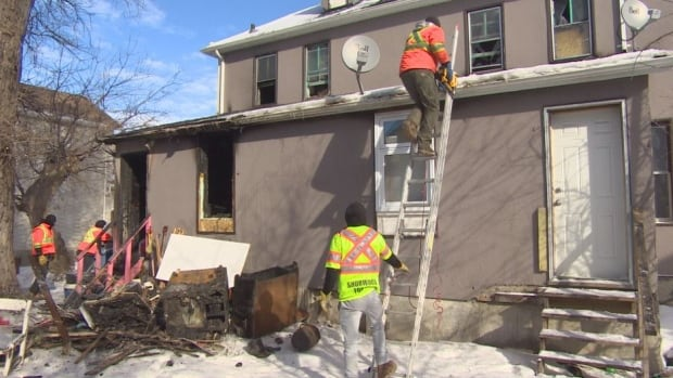 Crews at the rooming house on Alexander Avenue in the aftermath of the fire on Sunday.