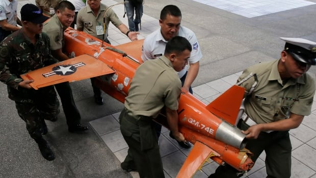 Soldiers carry a U.S. Navy target drone for presentation to the media Wednesday, Feb. 4, 2015, in the Philippines. The Trudeau government is quietly shopping for drones for the military and expects to see expressions of interest from the defence industry by mid-April.