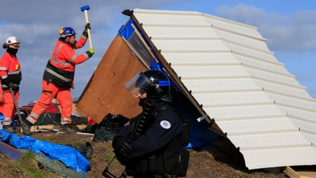 """A French riot policeman secures the area as workmen destroy a makeshift shelter during the partial dismantlement of the camp for migrants called the """"jungle"""", in Calais, France, on Monday."""