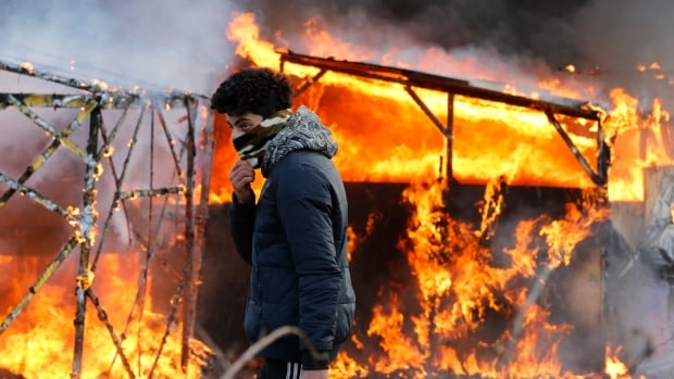 Protesters set huts on fire  as work began to clear the shanty town known as 'the jungle' outside the northern French city of Calais on Monday.
