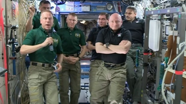 Tim Kopra, left, talks to NASA after officially taking command of the International Space Station, as Scott Kelly and Mikhail Kornienko, on the right, take part in a farewell ceremony on Monday.