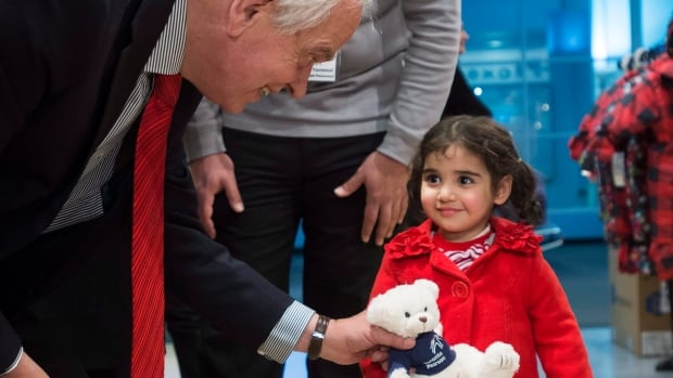 Immigration Minister John McCallum gives a bear to two-year-old Minisa at Pearson airport.
