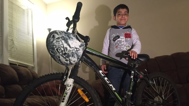 Abdo Al Oeteke, 12, poses with his new bicycle,  donated by the parents of a Calgary boy who died in 2014.