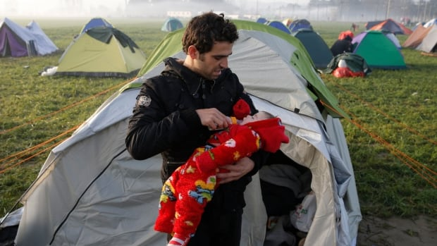 A man feeds a child at a makeshift camp set by stranded migrants waiting to cross the Greek-Macedonian border, near the Greek village of Idomeni on Tuesday.